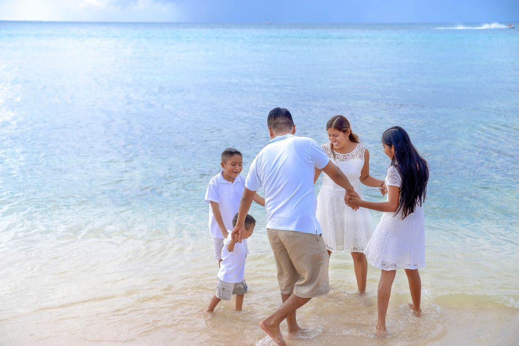 海辺で家族が輪になって手をつなぐ